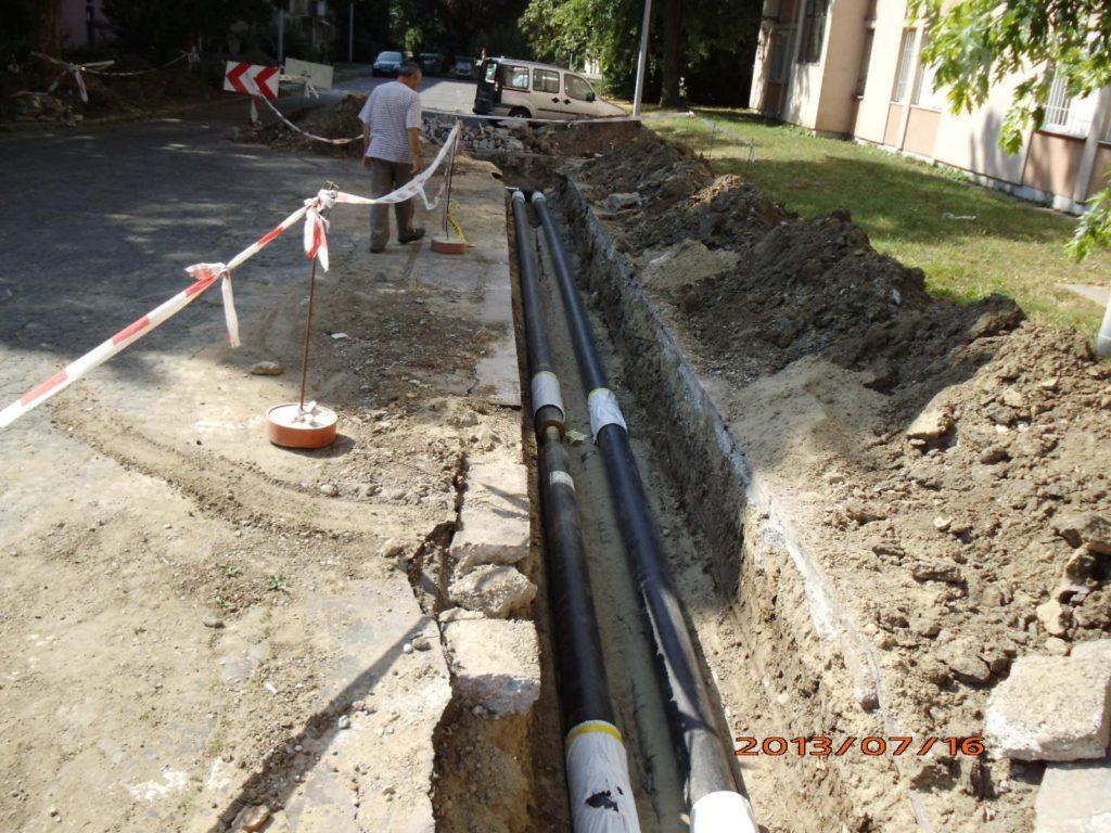A Mártírok úton a Gyermekkert Óvoda fölötti lakóépületek előtt mintegy 420 méter védőcsatornás vezetéket cserélt ki a T-Szol Zrt. korszerű, földbe fektethető, előszigetelt távhővezetékre. :